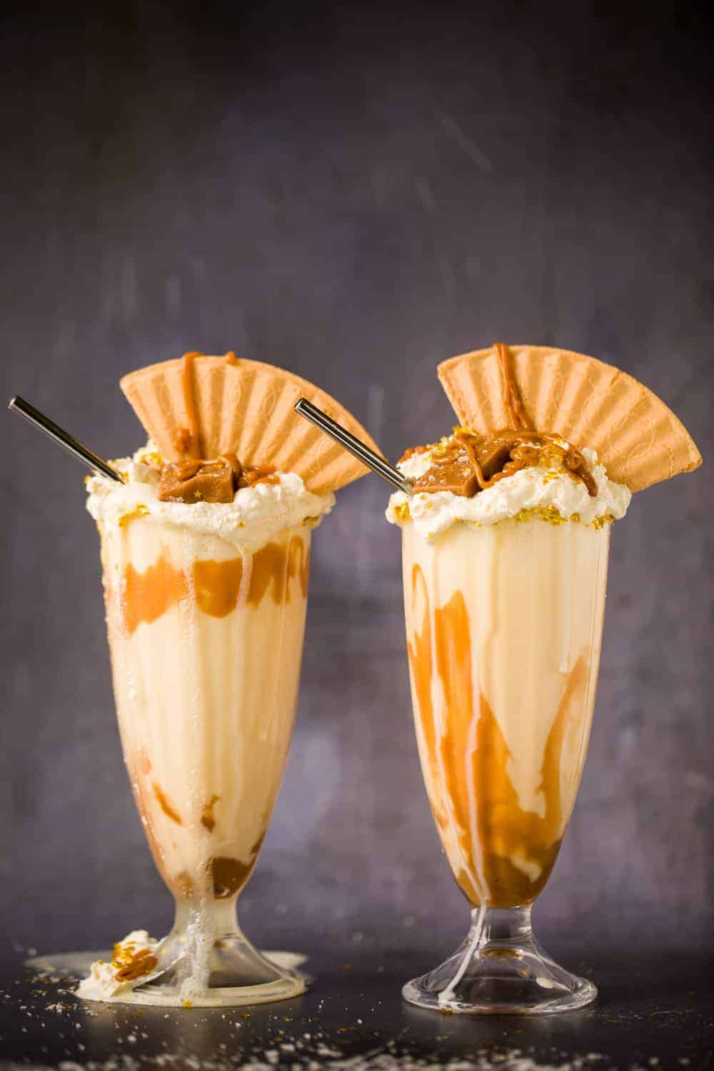 Two tall glasses filled with salted caramel milkshake. The glasses are topped with whipped cream, a wafer and pieces of salted caramel fudge.