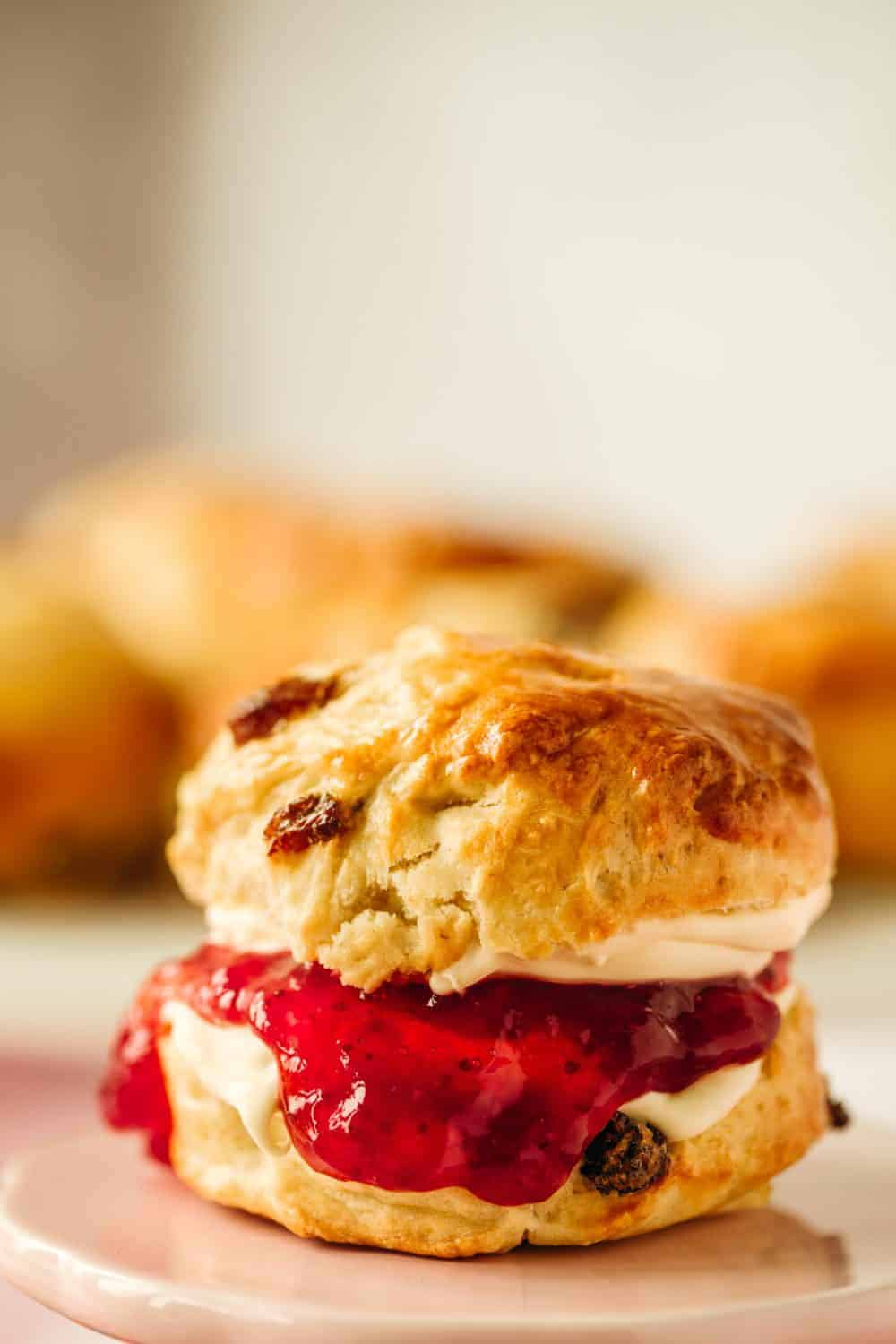 In the foreground is a scone that has been sliced in two and put back together. There is jam and cream dripping down the scone.