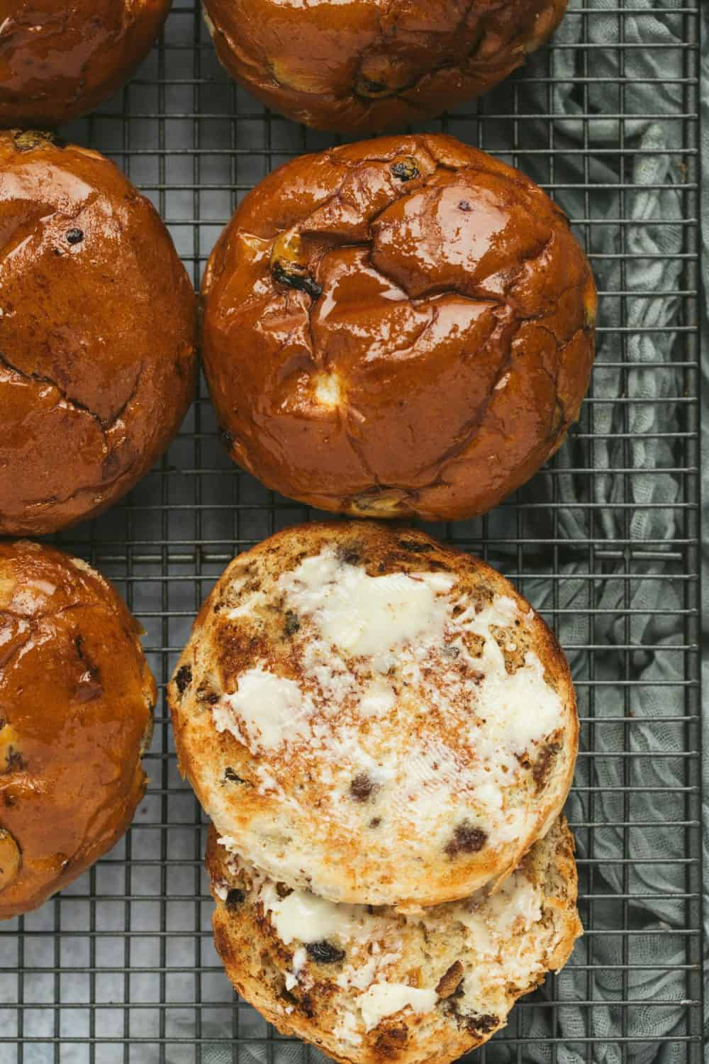 A toasted teacake spread with butter next to freshly baked teacakes.