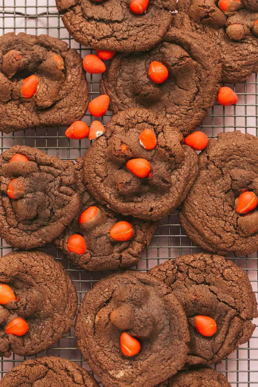 Overhead view of a batch of freshly baked chocolate mini egg cookies stuffed with orange mini eggs.