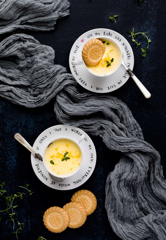 Two teacups with a lemon posset dessert inside