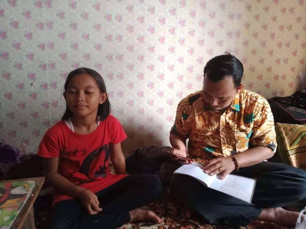Pak Aleh, guru SDN 4 Ciseureh Kecamatan Purwakarta sedang memeriksa buku tugas muridnya dirumah orang tua murid yang dikunjunginya, Rabu (10/3/2021)