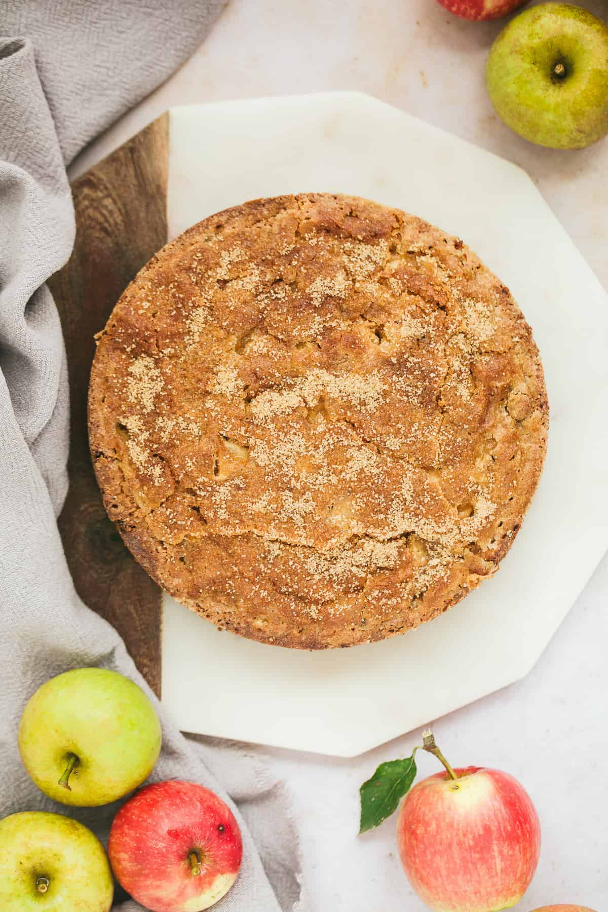A rustic looking cake with a crunchy sugar topping. The cake is on a chopping board and there are fresh apples surrounding it.