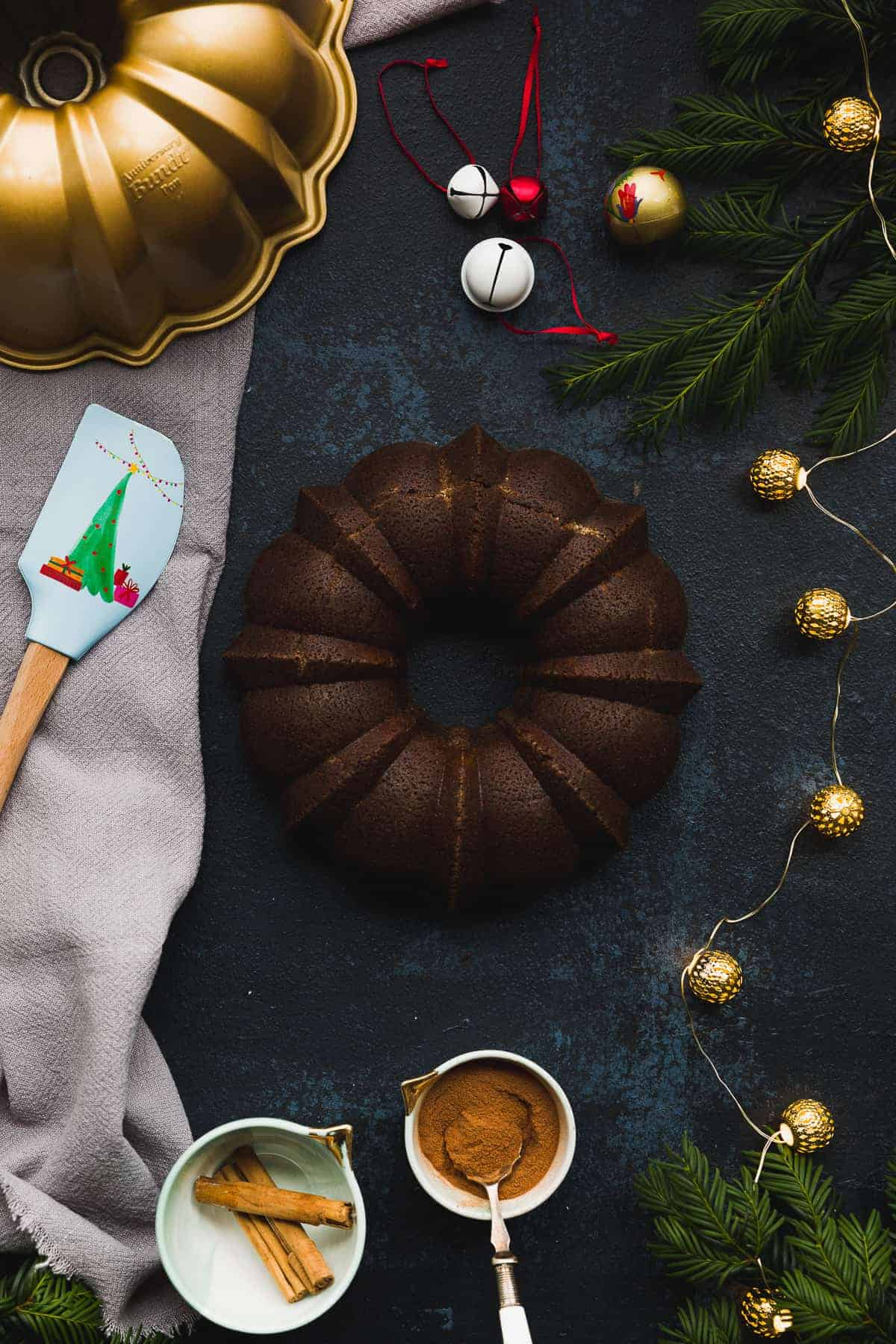 A black board with a gold bundt tin in the corner. In the centre is a dark coloured gingerbread bundt cake surrounded by christmas decorations and lights.
