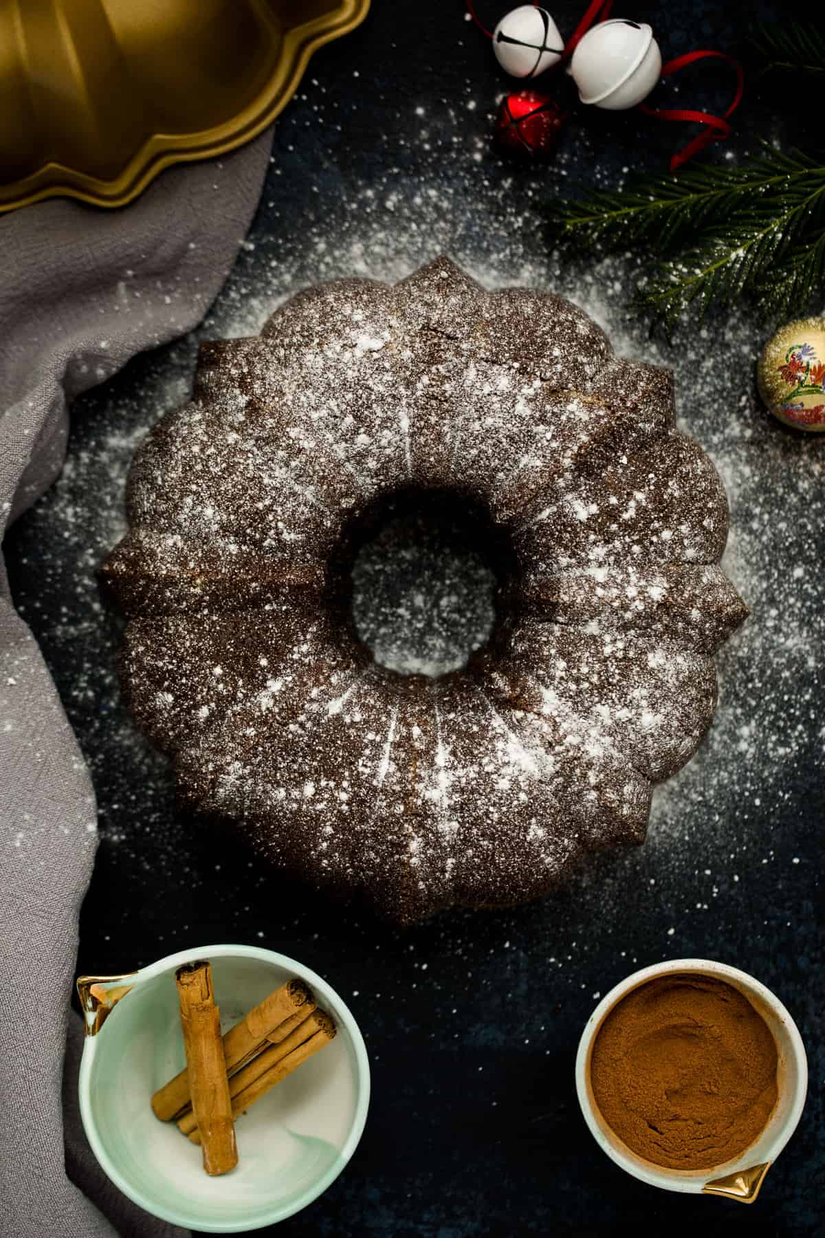 A black board with a gold bundt tin in the corner. In the centre is ginger cake in a circular shape, it has been dusted with icing sugar. It's surrounded by christmas decorations and lights.