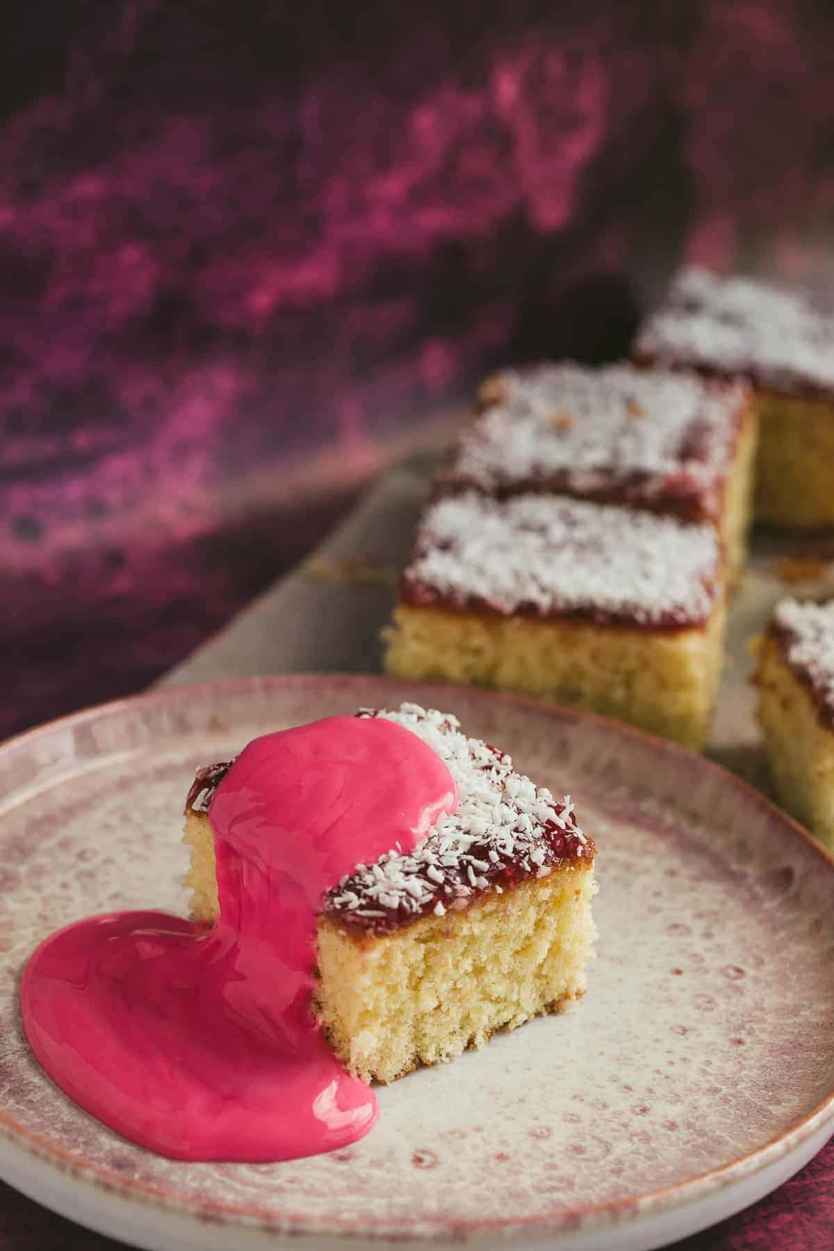 A slice of raspberry jam and coconut cake traybake