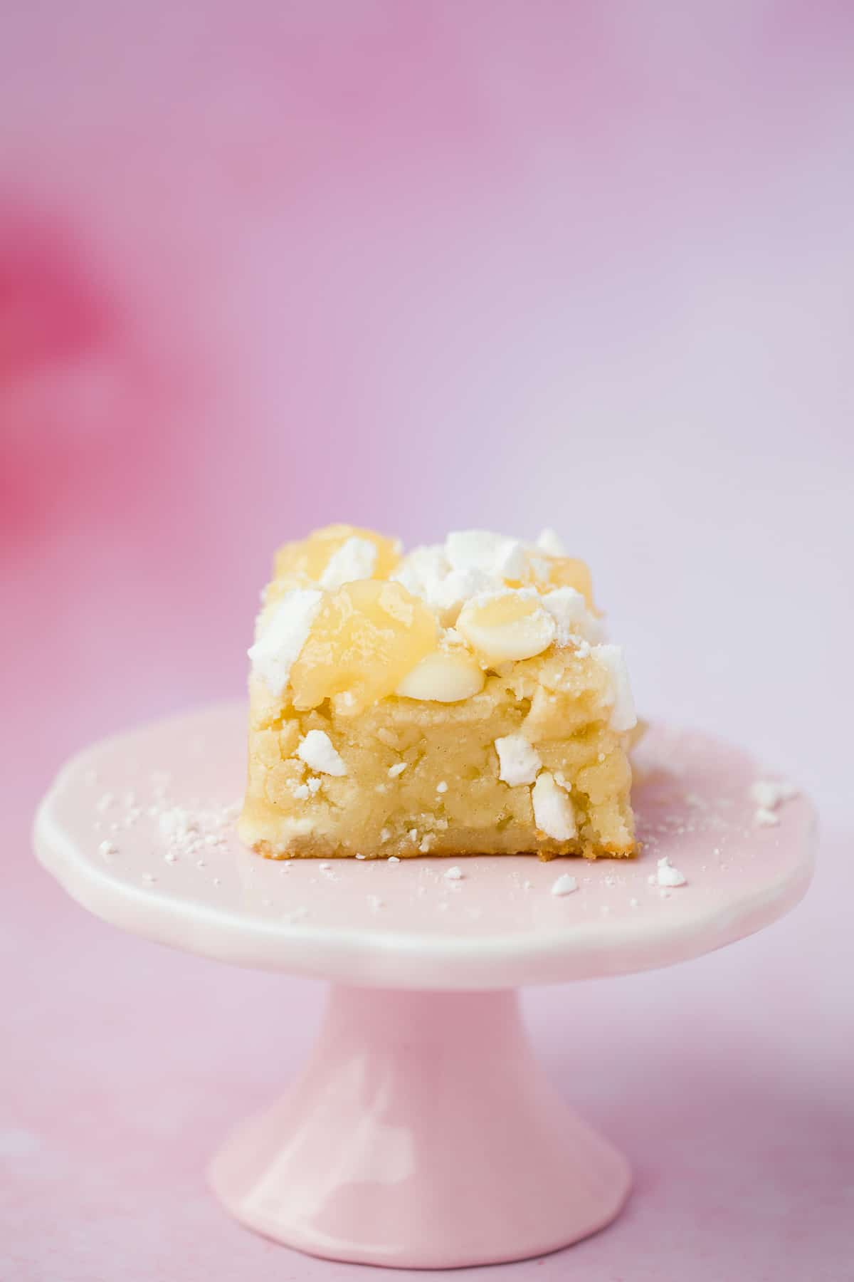 A lemon flavour blondie on a small pink cake stand.