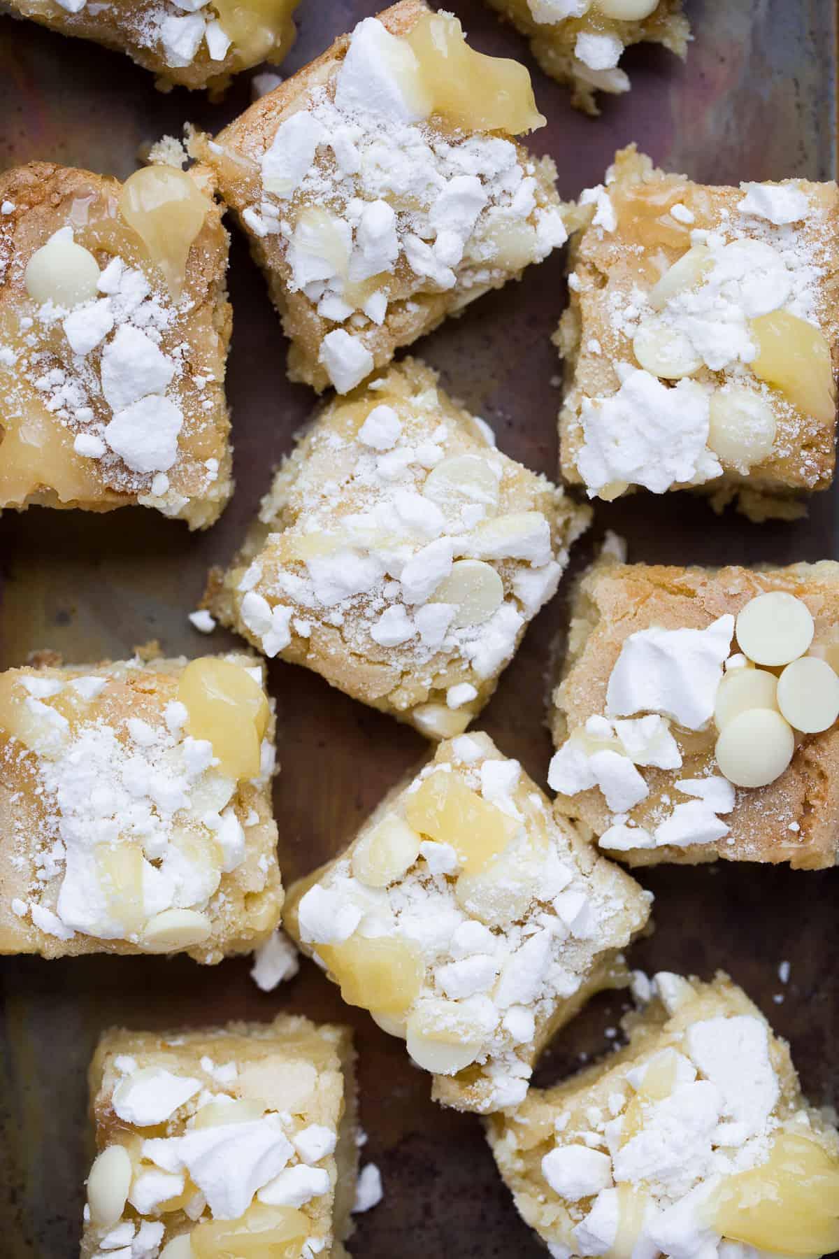 Squares of lemon meringue blondies on a dark coloured baking tray.
