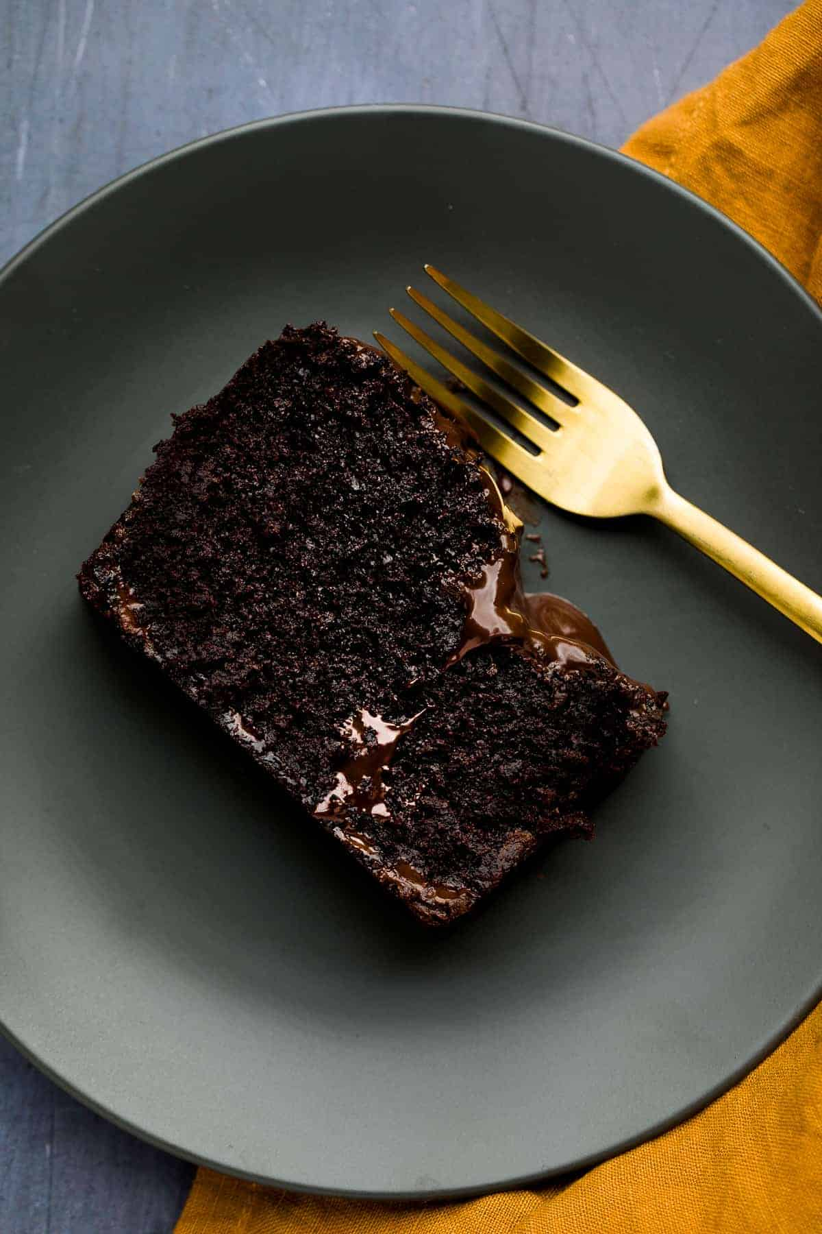 A slice of chocolate cake on a grey plate. There is melted chocolate oozing from the cake and a gold fork beside it.