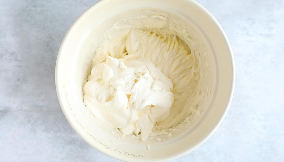 Double cream that has been whipped to stiff peaks has been added to a cream cheese mixture.