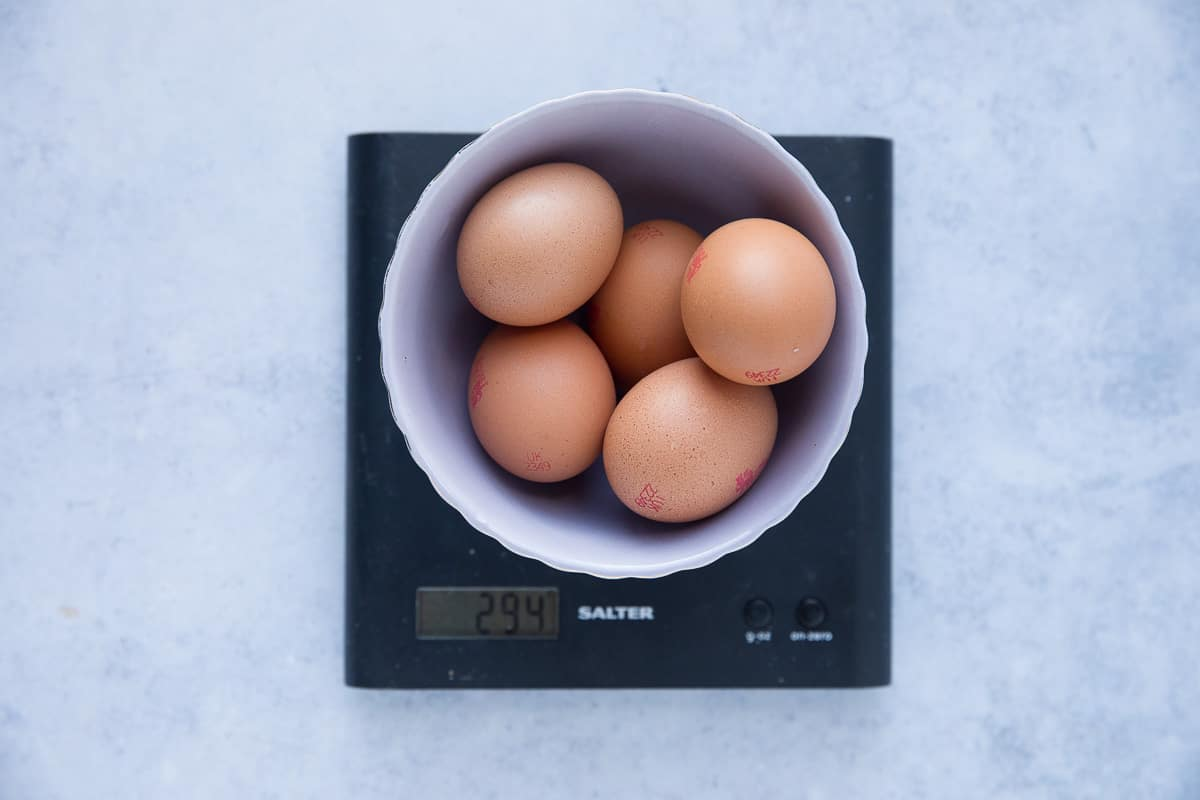 5 eggs in their shells inside a bowl that has been put onto a weighing scale.