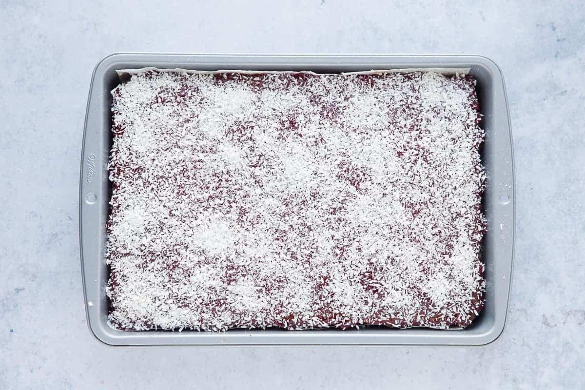 A traybake cake that has been sprinkled with desiccated coconut.