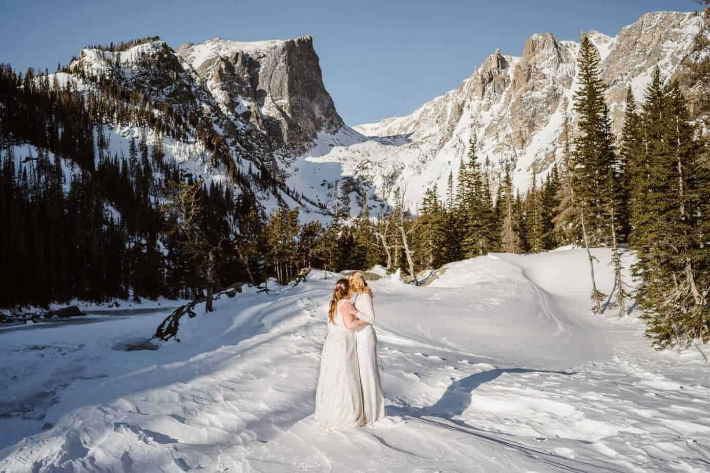 Bride and Bride Hugging Winter Elopement Guide