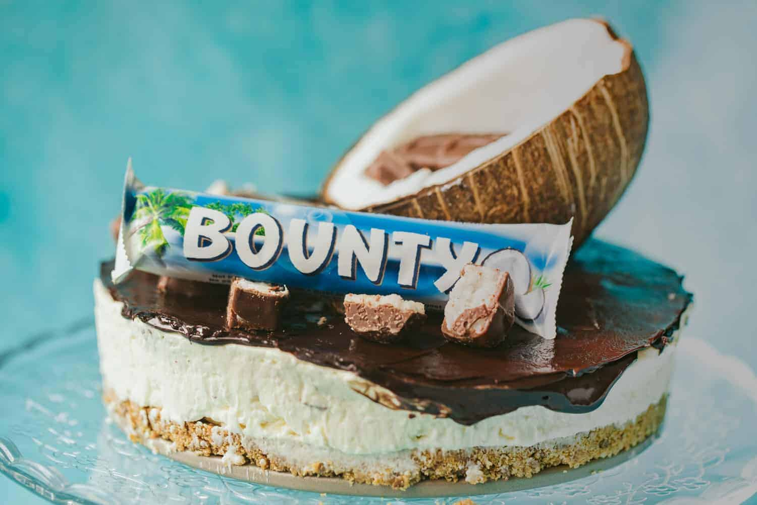 A cheesecake with chocolate ganache on top, half a coconut and Bounty bars are decorating the cheesecake