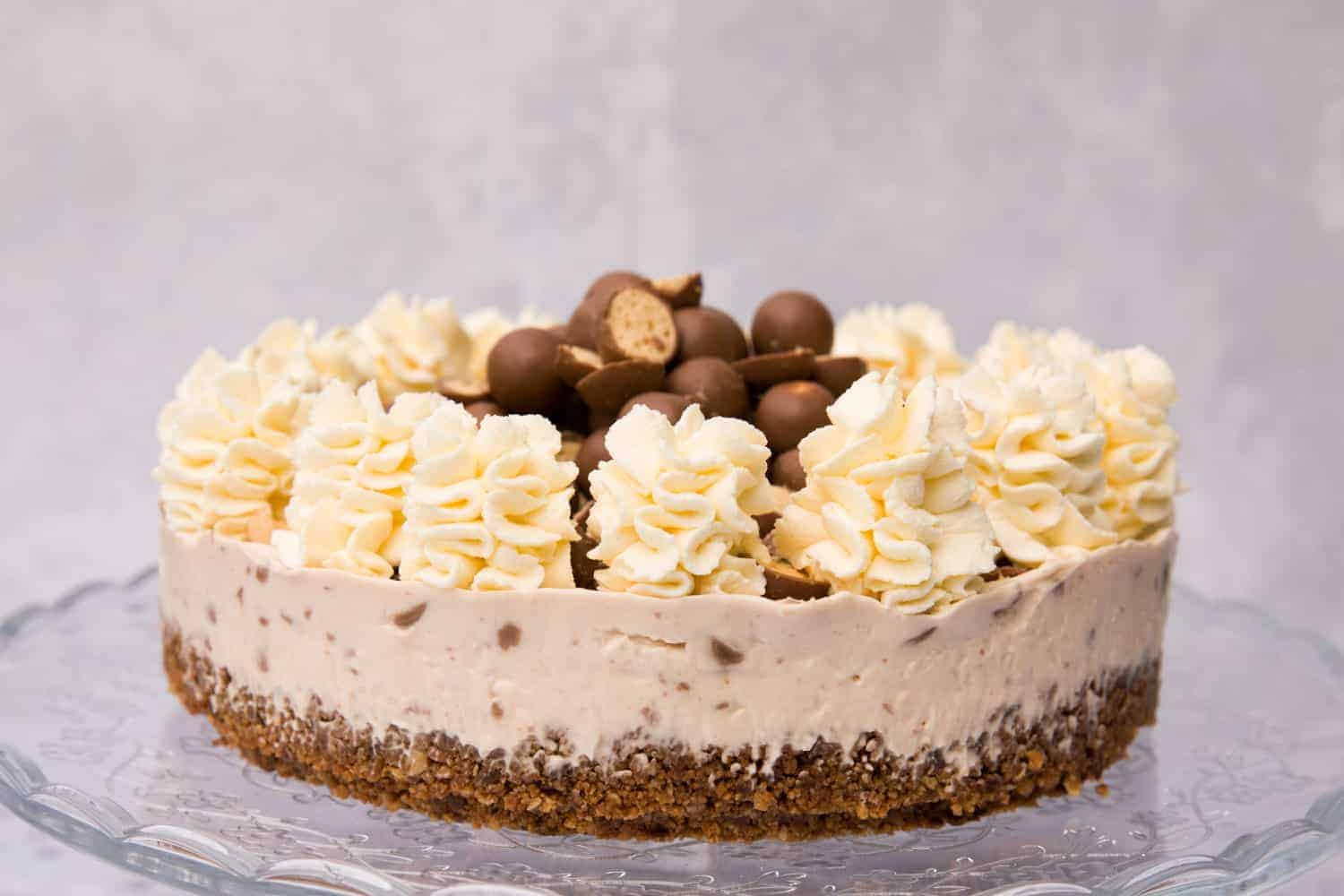 Side profile of a Malteser cheesecake. There is a chocolate biscuit base, cream cheese filling and piped swirls of double cream on top.