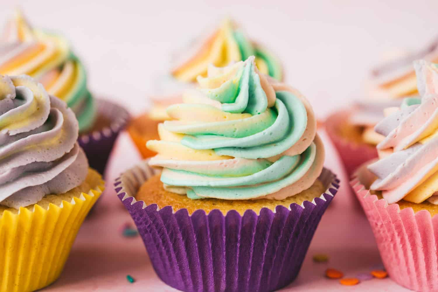 A row of piñata cupcakes topped with rainbow coloured icing