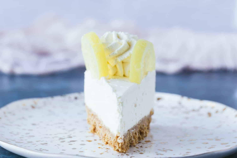A single slice of lemon cheesecake on a small dessert plate.