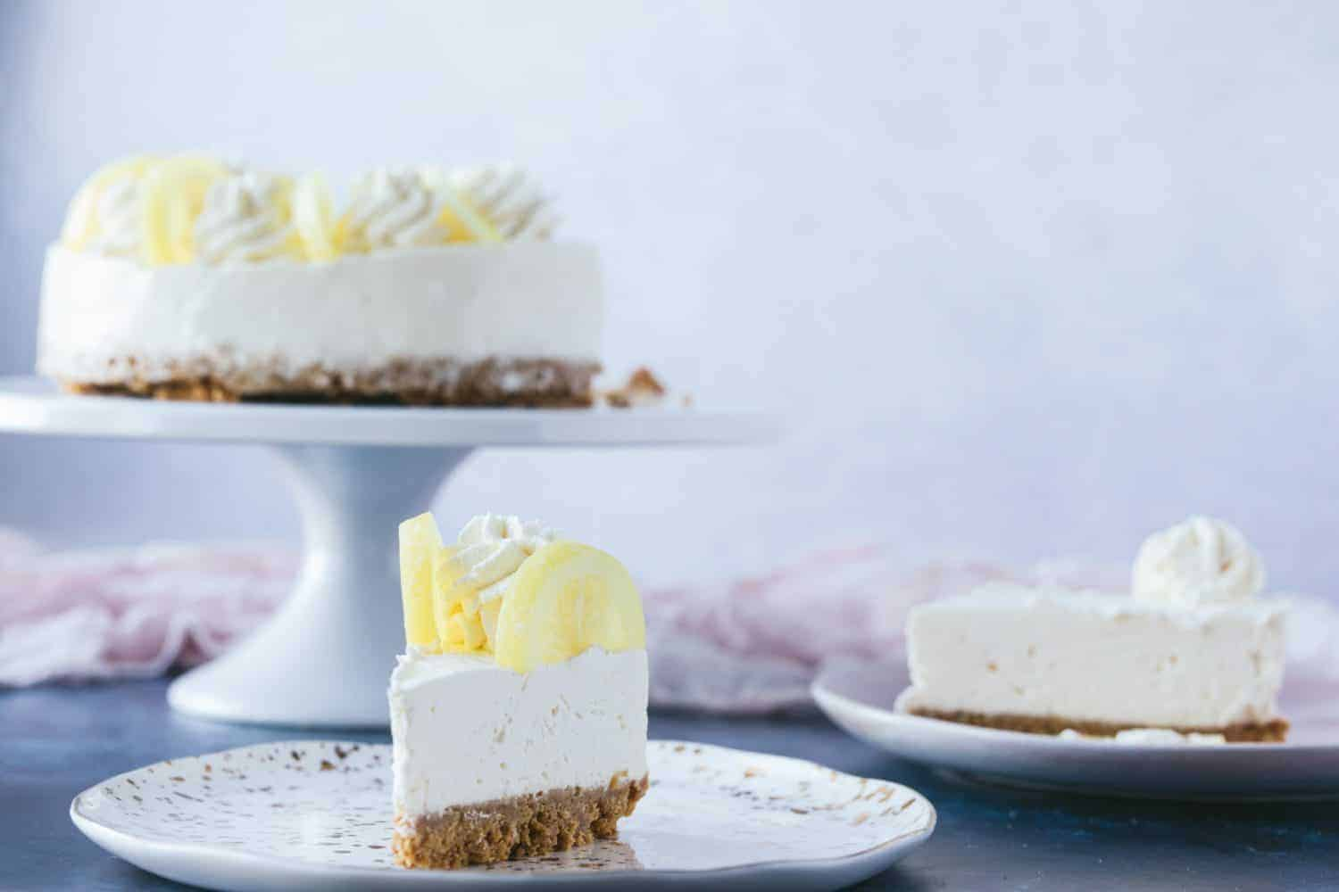 In the background is a cheesecake dessert on a white platter. In the foreground are two slices on small cake plates.