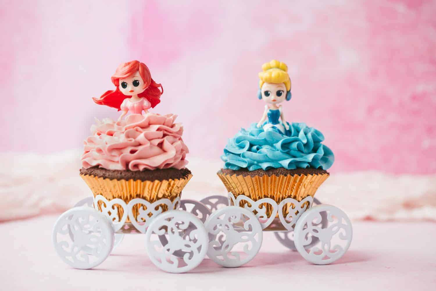 Two Disney Princess cupcakes sitting on chariot cupcake holders.