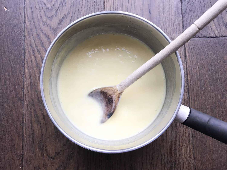 A saucepan with cream, lemon zest and lemon juice