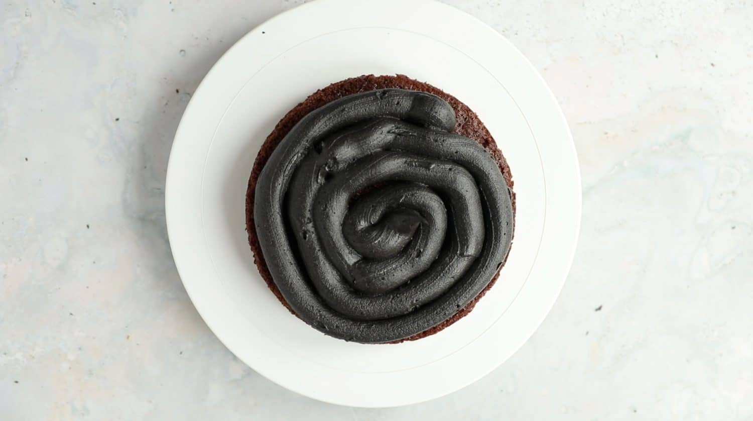 Overhead of a single layer of chocolate cake that has a spiral of black buttercream icing added to it.
