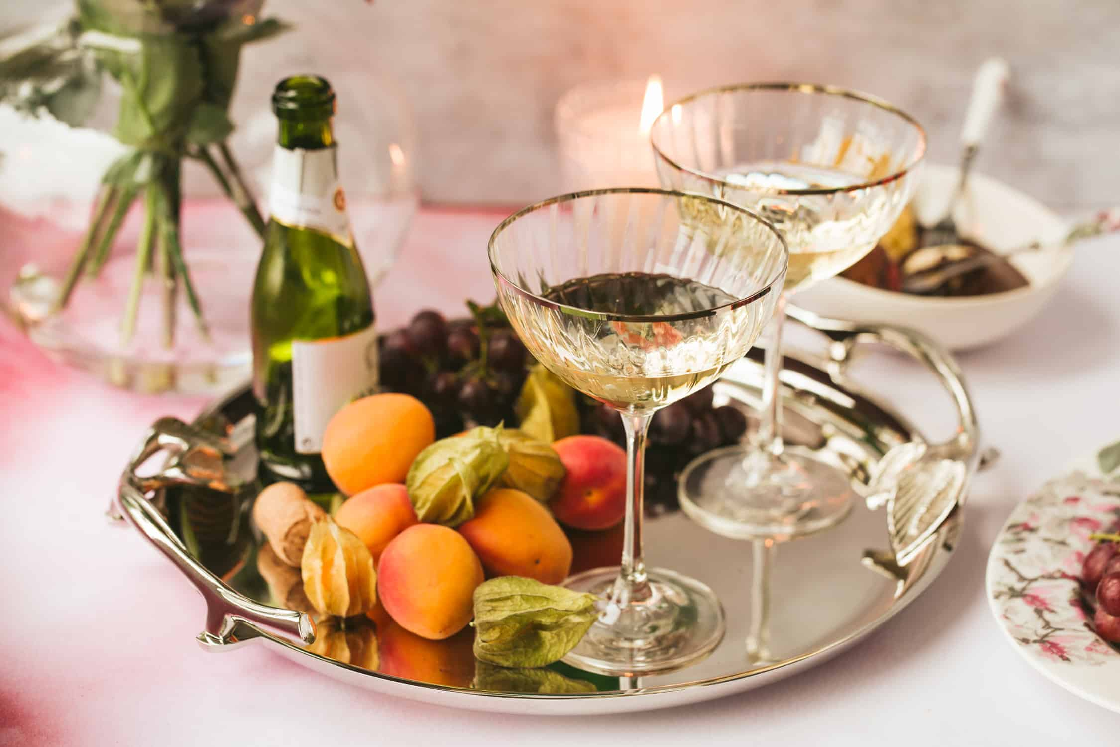 A silver tray with champagne saucers and fresh fruit.
