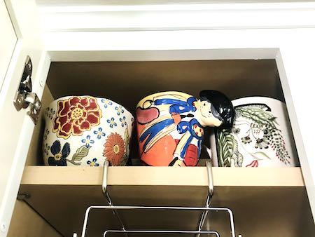 Organize glassware: pretty mugs in a cabinet