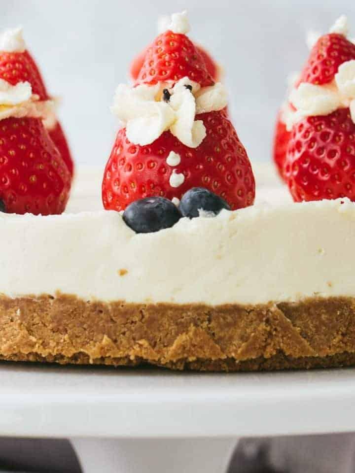 A white chocolate cheesecake with cream stuffed strawberry santas.