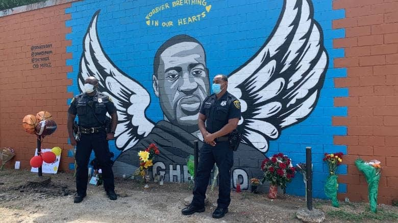 Two police officers pay their respects to George Floyd in Houston.
