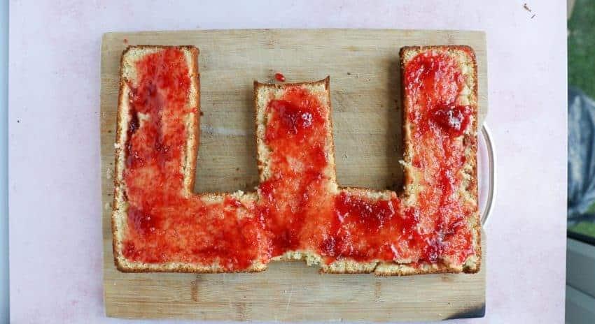 spreading strawberry jam onto a letter cake
