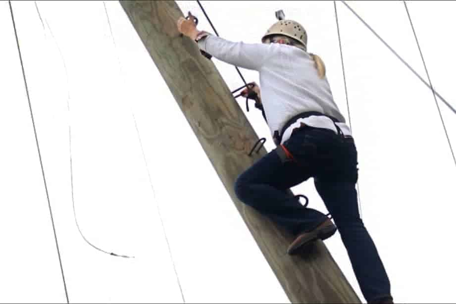 Woman climbing a zip line pole