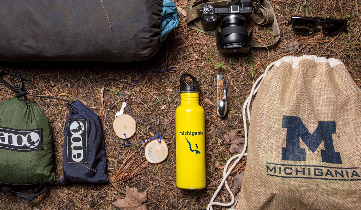 Camp Michigania bag and water bottle on the ground with sunglasses and a camera