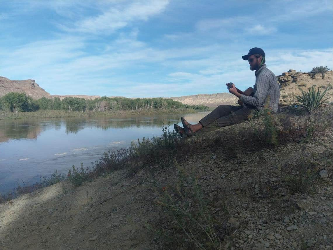 A geologist plays the guitar near a river.  Photo: Anya Metcalfe, USGS. Public domain.