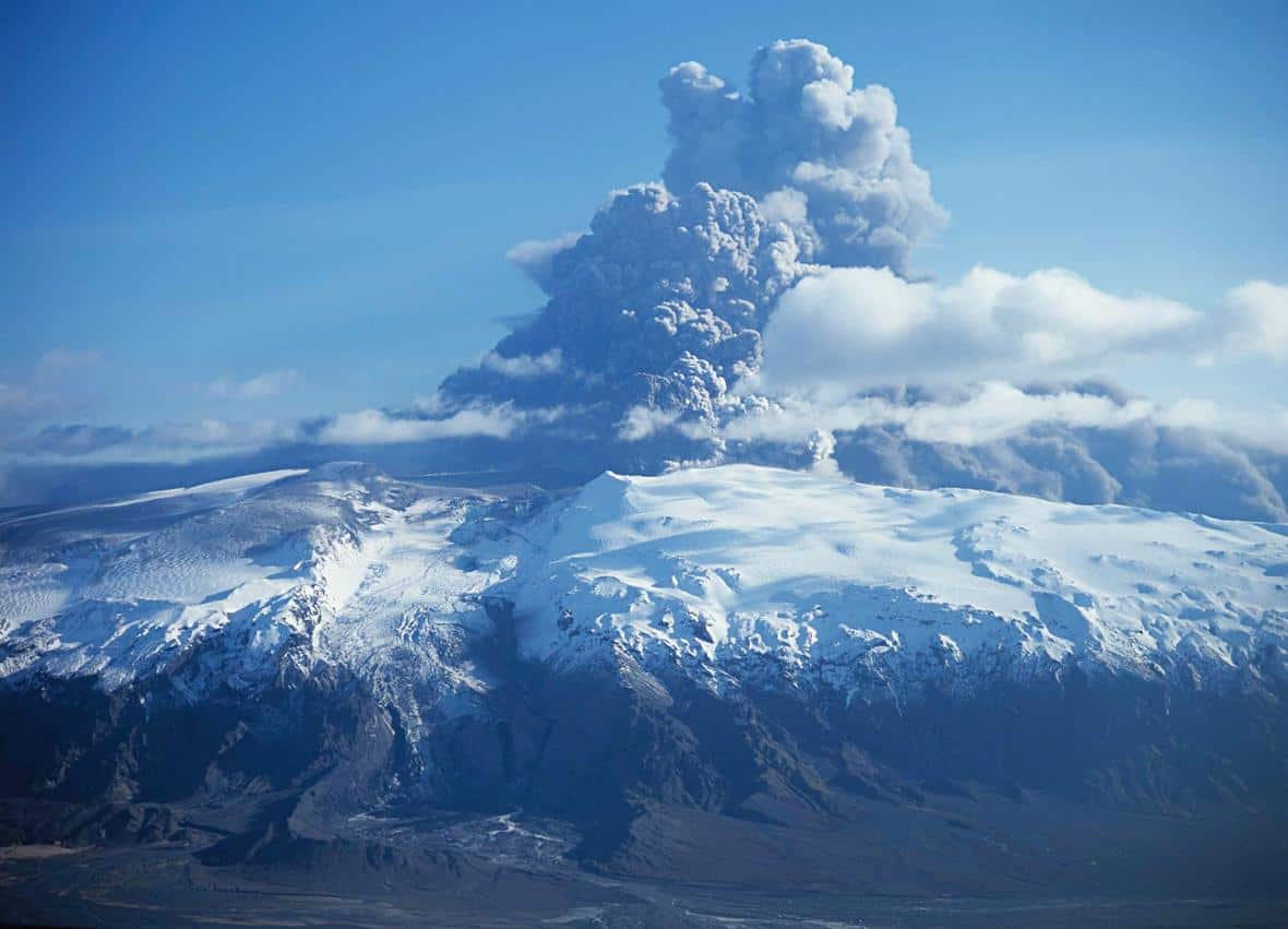 """Photograph of the eruption from the summit of Eyjafjallajökull from the north looking to the south across the Gígjökull outlet glacier, its """"missing"""" proglacial (ice-margin) lake caused by the jökulhlaup that filled in the lake. Photo: Oddur Sigurðsson, Iceland Meteorological Office. Public domain."""