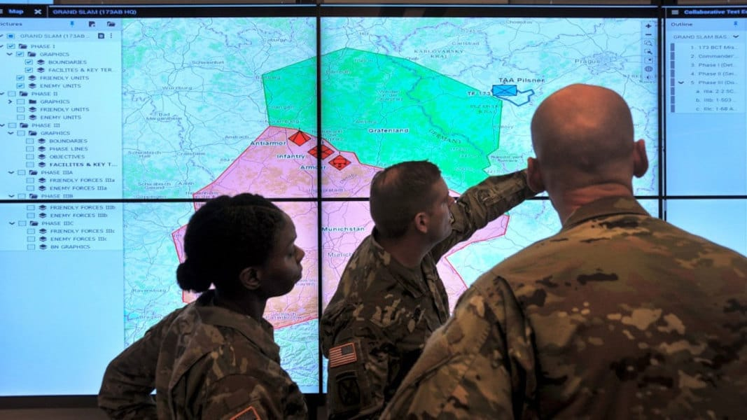 Photo of US soldiers looking at a digital map on a large screen.