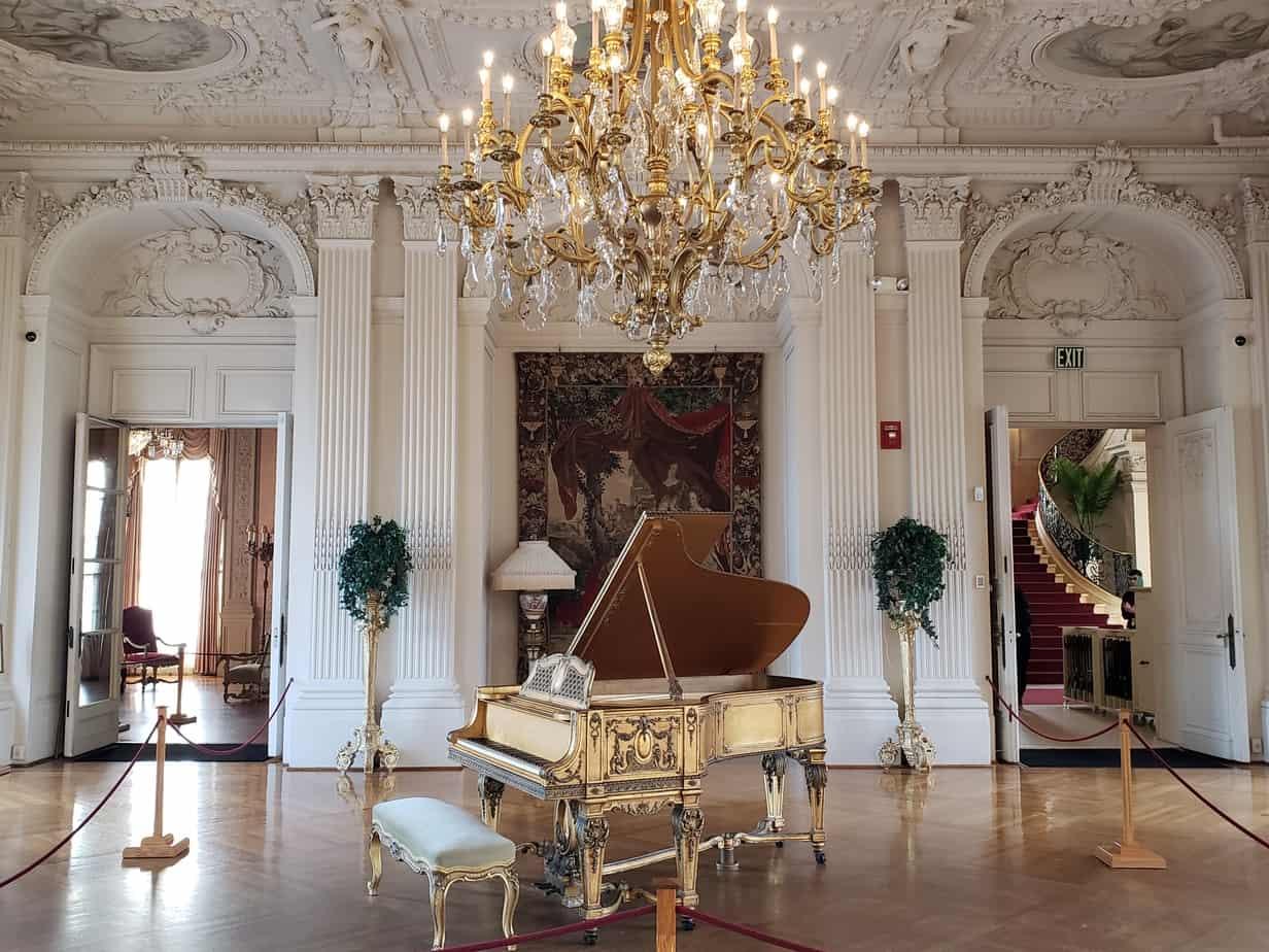 winter getaways in new england - visit the mansions of newport rhode island - photo of golden piano under chandelier