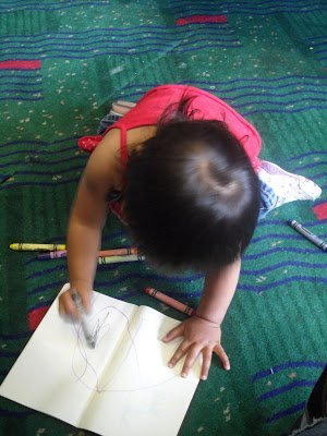 Child drawing at an airport while flying with a baby