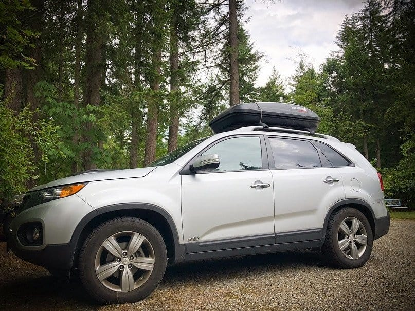 A silver SUV with a cargo box on the roof rests on a gravel driveway with pine trees in the background. One of the many gap year ideas for families is taking a road trip in a car and camping.