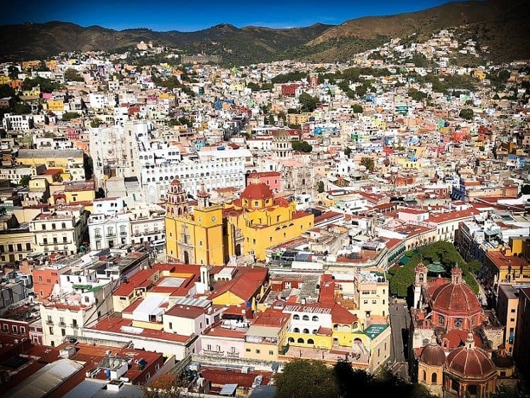 An aeriel view of Guanajuato, Mexico, an affordable world travel destination. In the center is a yellow church, with colorful buildings surrounding the church. The city is set in a valley, with hills in the distance.