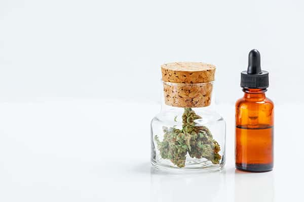 Medical cannabis in glass jar with Cannabidiol oil next to it.