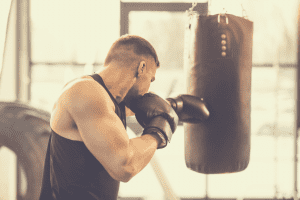 a male boxer punching heavy bag