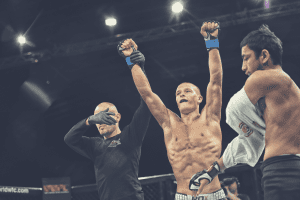 winning fighter holding arms up in celebration