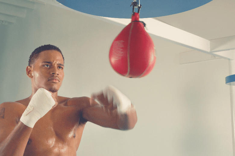 male boxer punching red speed bag