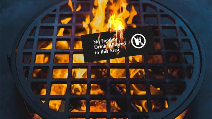 A barbecue pit with a fire inside and on top sits a sign that reads no food or drink in the area that is also on fire