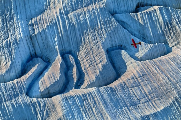 A plane flying over a river of meltwater on glacier in Alaska