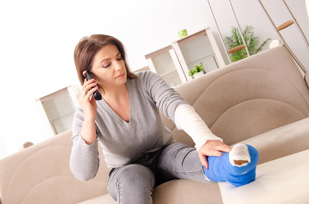 photo of a woman recovering at home after a car accident, talking with her car accident lawyer about her settlement