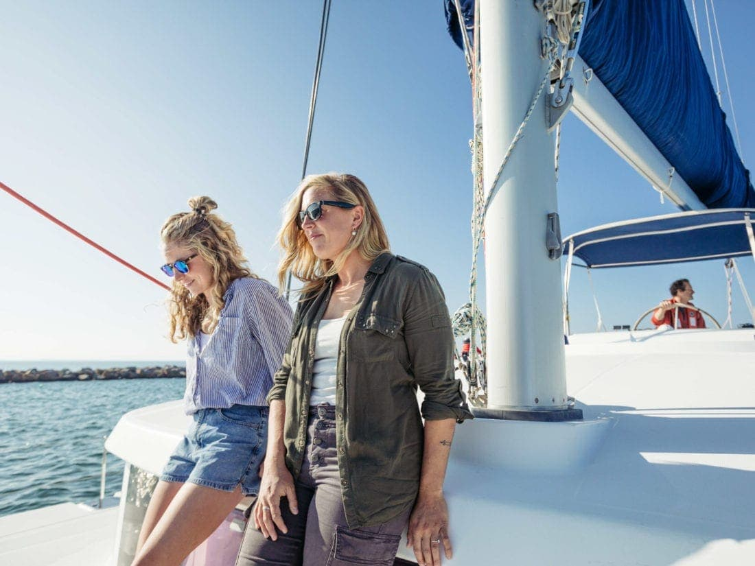 two blonde women standing at mast on catamaran