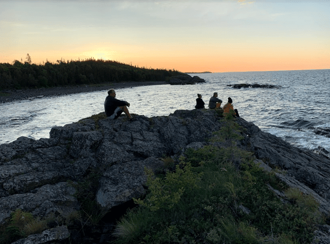 sitting on roak outcrop at sunrise on battle island
