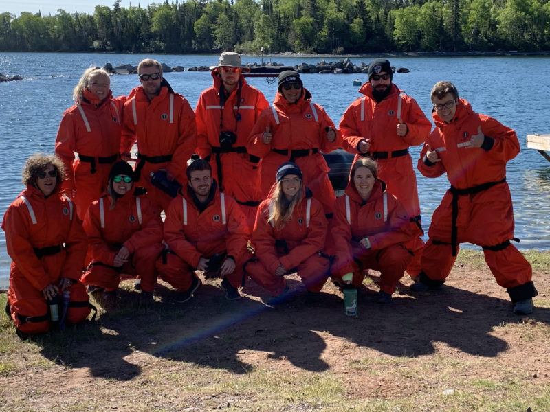Group of Zodiac passengers in mustang floater suits on shore at Silver Islet