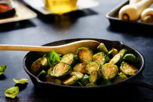 brussel sprouts and wooden spoon in cast iron skillet on black table